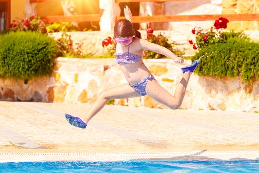 Happy girl jumping to the pool