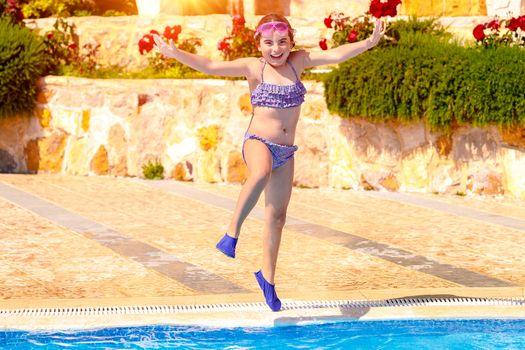 Joyful girl jumping to the pool