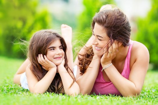 Portrait of a mother with little pretty daughter having fun together outdoors, lying down on the meadow and looking on each other, spending summer holidays in a countryside, happy family life
