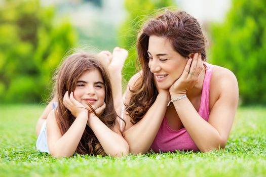 Portrait of a mother with little pretty daughter having fun together outdoors, lying down on the meadow, relaxing in a countryside, happy family life