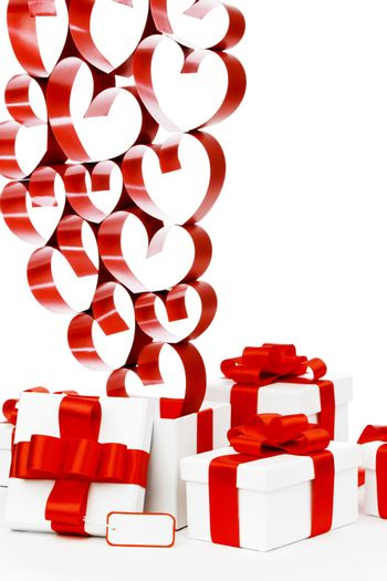 Gifts in white boxes with red ribbons and hearts isolated on white background