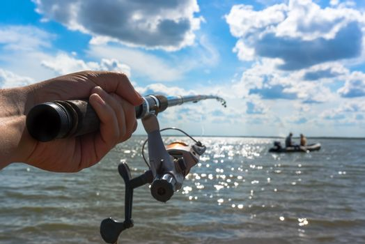 a fisherman catches a fish. Hands fisherman keep spinning rod close-up