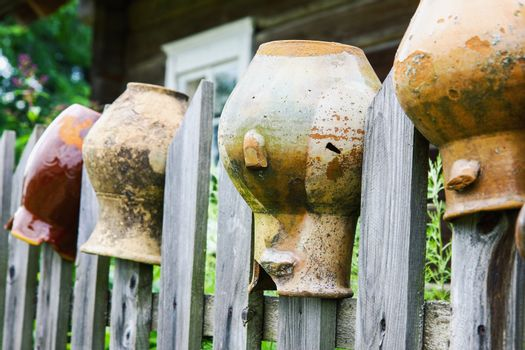 Old broken clay jugs on wooden fence in rural environment