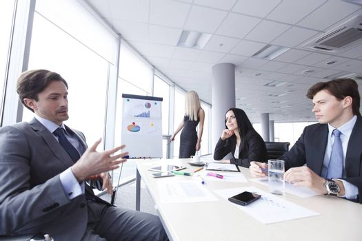 Workers at business meeting looking at presentation of financial reports in modern office
