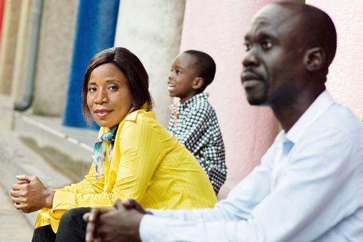 This young woman sitting and framed by her child and her husband watched the camera.