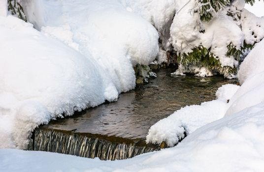 brook with cascades in winter