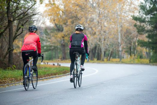 Two Young Female Cyclists Riding Road Bicycles in the Park in the Cold Autumn Morning. Healthy Lifestyle Concept.
