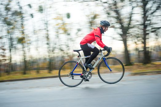 Young Woman in Bright Orange Jacket Riding Road Bicycle in the Park in the Cold Autumn Day. Healthy Lifestyle Concept.