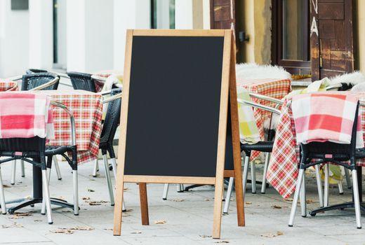 Blank menu chalkboard mockup on the street with empty cafe seats