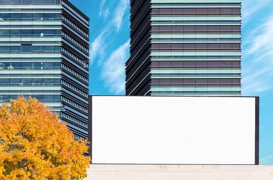 Blank large outdoor billboard mockup with modern business buildings in background on bright autumn day