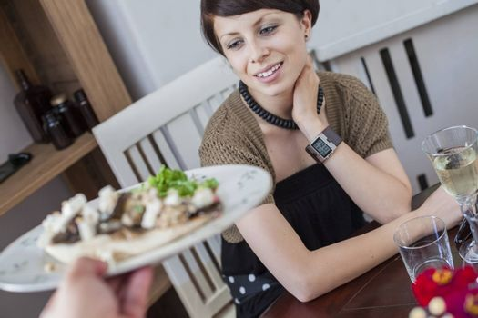 A young beautiful female is being served in a restaurant.