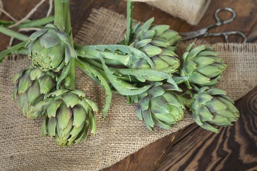 Two artichoke bouquets on sackcloth on wooden background. Top vi
