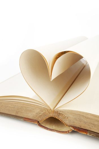 Heart shaped book pages on white background