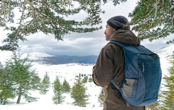 Traveler man in the snowy mountains