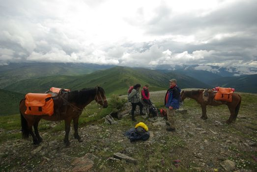 Orlov village, Altai, Russia - June 29, 2016: People with horses Horses walk and graze