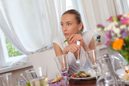 A beautiful female is sitting in restaurant behind glasses and a dish of appetizers.