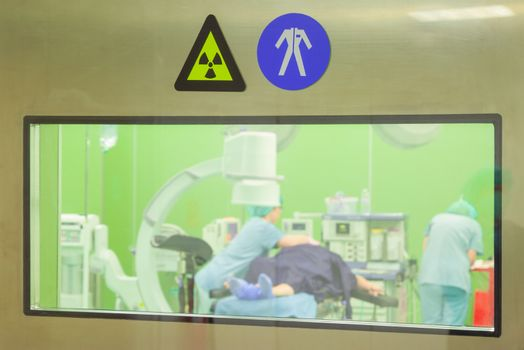 A sign for radiation and work clothes on a door of a surgery room while patient being prepared for operation.