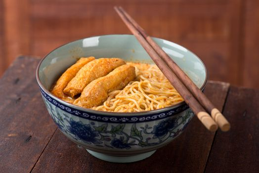 Curry Laksa with chopsticks, which is a popular traditional spicy noodle soup from the culture in Malaysia.
