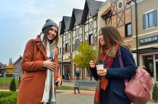 two girlfriends laugh standing in the street