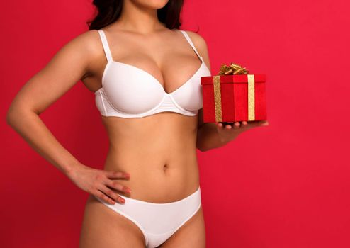 Sexy voluptuous busty woman in white lingerie holding a gift box, red background