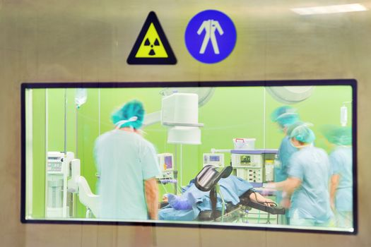 A view through the door window of a modern urology surgery with patient and motion blurred figures of doctors and nurses.