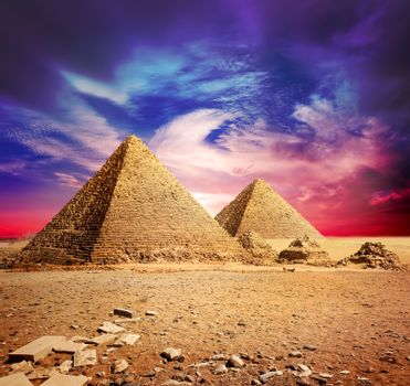 Pyramids in desert under ultra violet clouds