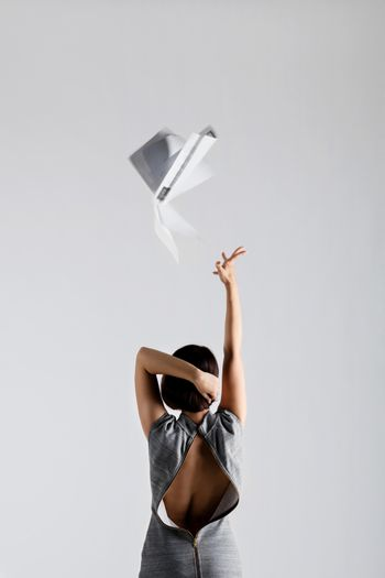 girl throwing papers