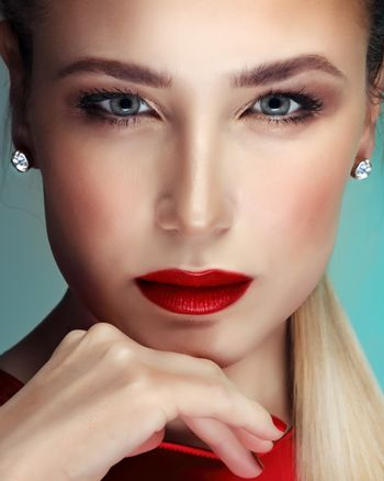 Closeup portrait of a beautiful blond woman with classic evening makeup, attractive model with red lips and red nail polish, perfect professional face makeover