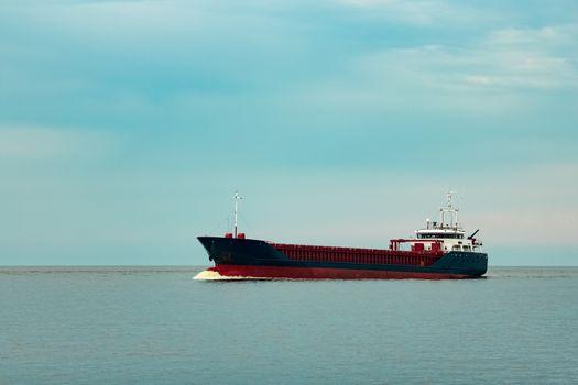 Merchandise import. Large blue cargo ship moving to Riga port