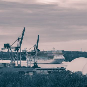 Large cruise liner sailing past the cargo port. Monochrome