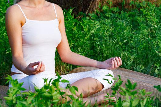 Yoga woman sitting in green grass