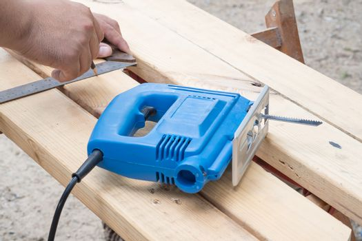 Master cuts wood with a jig saw.