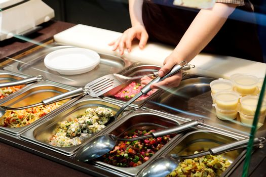 Trays with cooked food on showcase at cafeteria. Salad variety at a buffet