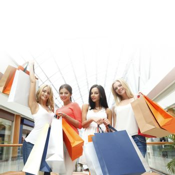 Happy young women with shopping bags posing in mall