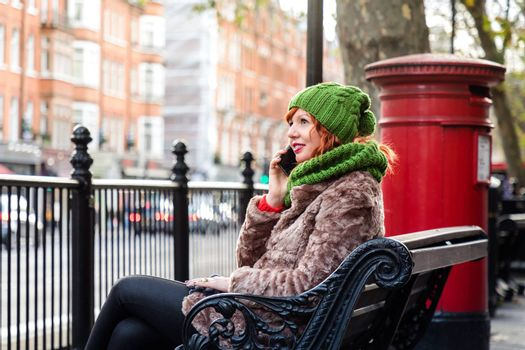 Woman sitting on bench on London street have a chat with friends over mobile