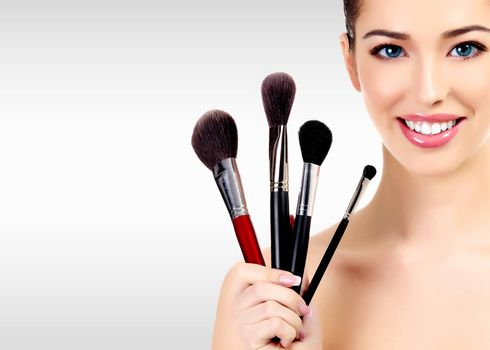 Beauty portrait of lovely beautiful happily smiling woman holding a bunch of make-up brushes against a grey background with copyspace