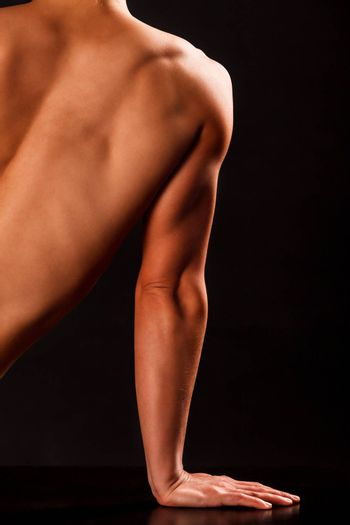 Arm and part of back of muscular woman posing against black background