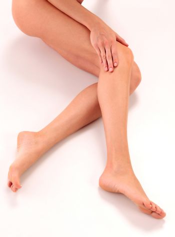 Closeup shot of healthy naked woman legs with soft clear skin on white floor
