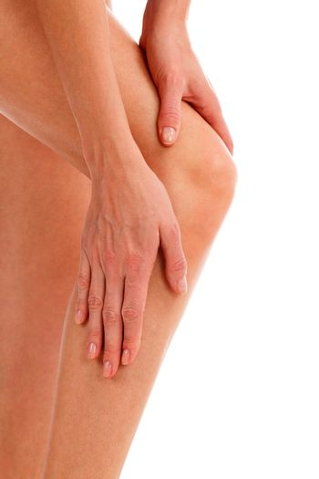 Closeup shot of woman holding sore knee, isolated on white background