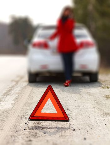Woman standing by the broken car and warning triangle sign