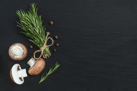 Rosemary bunch of bouquets, mushrooms and fragrant pepper on bla