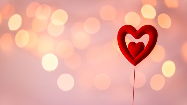 Love you concept, closeup photo of a little red heart shaped toy over blurry pink bokeh background, dreamy romantic postcard, greeting card with love for Valentines day holiday