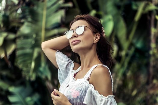 Portrait of a gorgeous woman in rainforest, attractive sexy model wearing stylish sunglasses, luxury photoshoot in the jungle, enjoying summer vacation on exotic island
