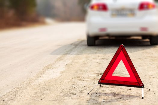 Red triangle sign and automobile on the road, shallow depth of view