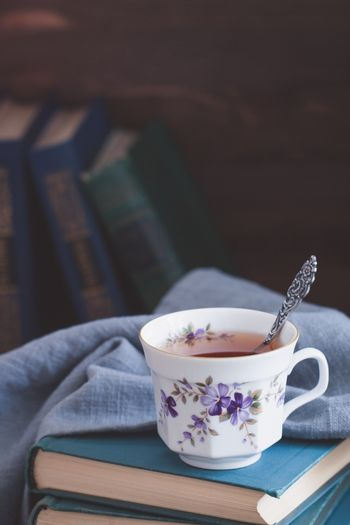 Old porcelain cup with tea on old books