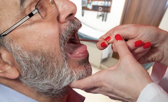 Adult with doctor in pediatrician office, medical examination of sore throat.