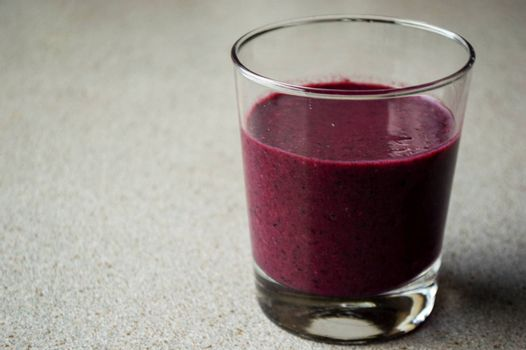 Purple smoothie with berries and fruit in glass on a grey table.