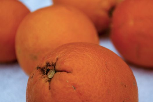 Fresh orange oranges on white background. Out of focus.