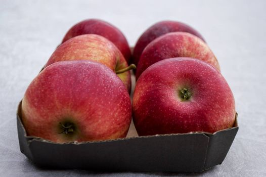 Box filled with fresh organic red apples on white background.