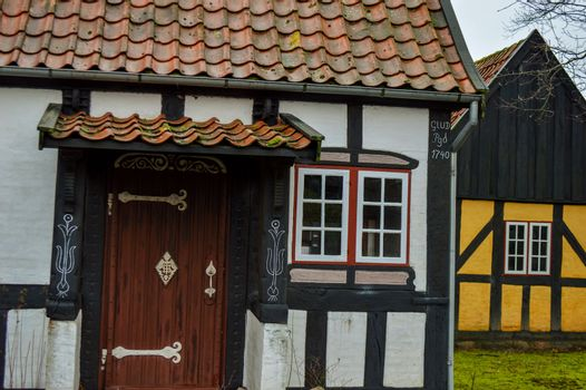 A white half-timbered house with an old door and a yellow half-timbered house in the background on a cloudy day.